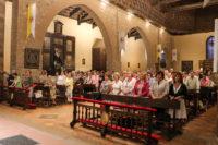 Aspecto del templo parroquial, con la presencia de la Hermandad de los Santos en primera fila